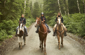 Two women and a girl horseback riding on dirt road